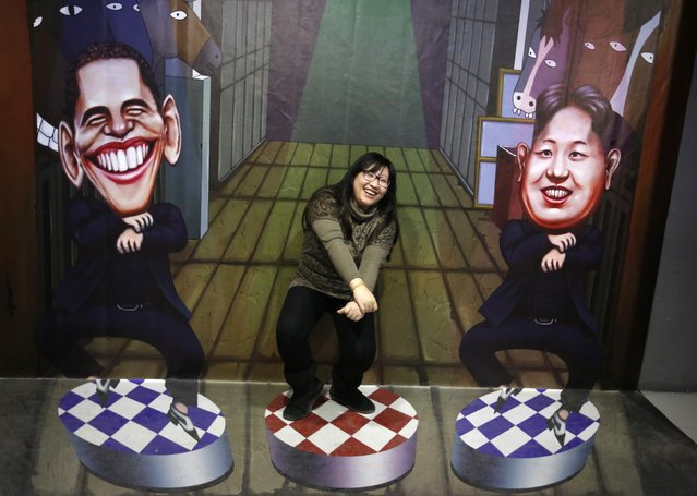 A visitor poses for a photograph in front of a 3D painting depicting U.S. President Barack Obama (L) and North Korean leader Kim Jong-un at a 3D art gallery in Beijing January 16, 2015. The gallery attracts visitors with various 3D paintings and installations depicting world famous political leaders, celebrities and movie scenes. (Photo by Kim Kyung-Hoon/Reuters)