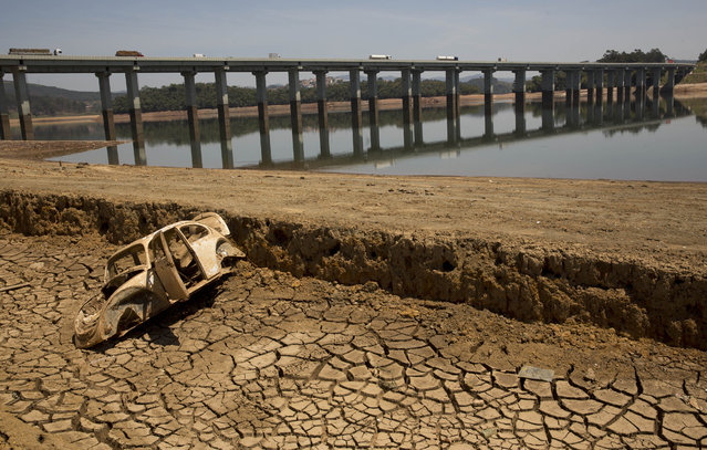 In this October 10, 2014 file photo, the frame of a car sits on the cracked earth at the bottom of the Atibainha dam, part of the Cantareira System responsible for providing water to the Sao Paulo metropolitan area, in Nazare Paulista, Brazil. Halfway through the rainy season, the key reservoir for the hemisphere's largest city, the Cantareira water system, holds just 6 percent of its capacity. (Photo by Andre Penner/AP Photo)