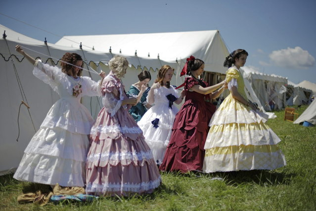 Women in Civil War era ball gowns help each other undress during ongoing activities commemorating the 150th anniversary of the Battle of Gettysburg, Saturday, June 29, 2013, at Bushey Farm in Gettysburg, Pa.  Union forces turned away a Confederate advance in the pivotal battle of the Civil War fought July 1-3, 1863, which was also the war s bloodiest conflict with more than 51,000 casualties. (Photo by Matt Rourke/AP Photo)