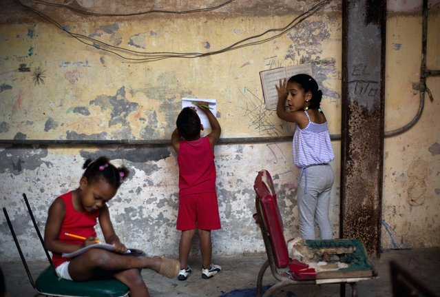 Kids do their homework inside the courtyard of an apartment building in Havana, Cuba, Monday, January 19, 2015. Cuba has so far offered a guardedly positive reception to President Barack Obama's loosening of the trade embargo on Cuba, saying it welcomes the full package of new economic ties on offer, but it insists it will maintain its one-party political system and centrally planned economy. (Photo by Ramon Espinosa/AP Photo)