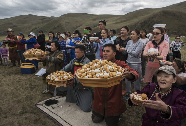 Mongolian followers of Shamanism or Buu murgul, pray during a blessing as part of a Zugel ritual ceremony in the grasslands on June 21, 2018 outside Ulaanbaatar, Mongolia. (Photo by Kevin Frayer/Getty Images)