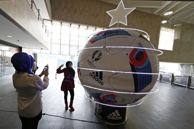 """Youths take pictures near a decorated giant UEFA Euro 2016 soccer ball, dubbed """"Beau Jeu"""" (Beautiful Game), in downtown Beirut, Lebanon December 17, 2015. (Photo by Jamal Saidi/Reuters)"""