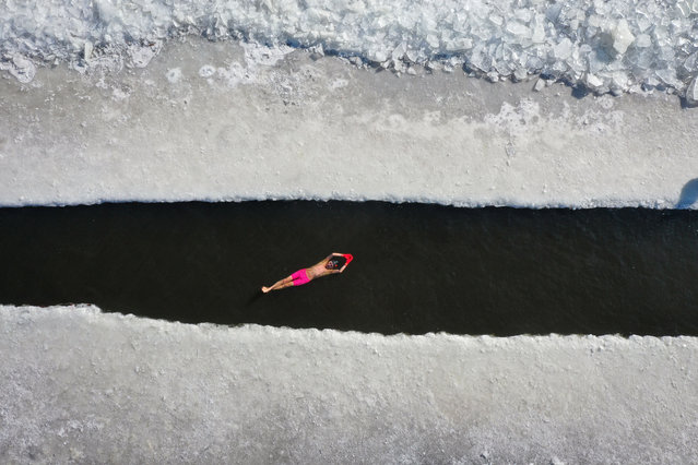 This aerial view shows a man swimming in a pool cut in a frozen lake in Shenyang, in China's northeastern Liaoning province on January 7, 2021. (Photo by AFP Photo/China Stringer Network)
