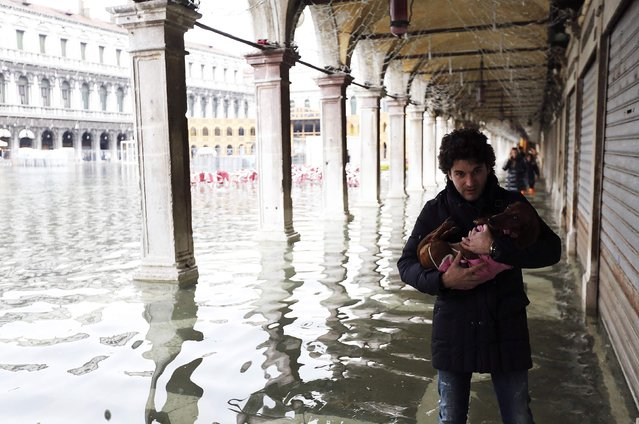 A man carries his dog as he walks through the flooded St. Mark's Square during a period of seasonal high water and on the first day of carnival, in Venice February 1, 2015. (Photo by Stefano Rellandini/Reuters)
