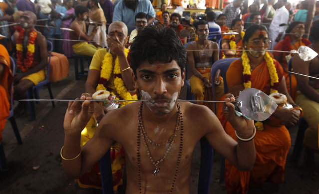 A Hindu devotee sits with his cheeks pierced with a metal rod as he participates in a religious procession during Thaipusam festival in Chennai, India, Tuesday, February 3, 2015. (Photo by Arun Sankar K./AP Photo)