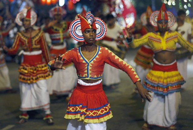 Traditional dancers performs at Navam Perahera, a Buddhist pageant of elephants, dancers and drummers, in Colombo February 3, 2015. Over 50 elephants participated in the street parade for Gangaramaya temple's annual Perahera festival, along with a nightly procession of traditional dancers, fire twirlers and traditional musicians. (Photo by Dinuka Liyanawatte/Reuters)
