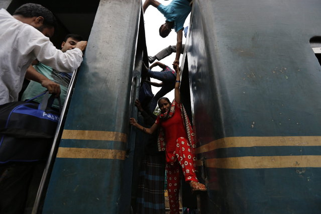 A woman tries to climb on board an overcrowded train at a railway station in Dhaka August 8, 2013. Millions of residents in Dhaka are travelling home from the capital city to celebrate the Muslim Eid al-Fitr holiday, which marks the end of the holy fasting month of Ramadan. (Photo by Andrew Biraj/Reuters)