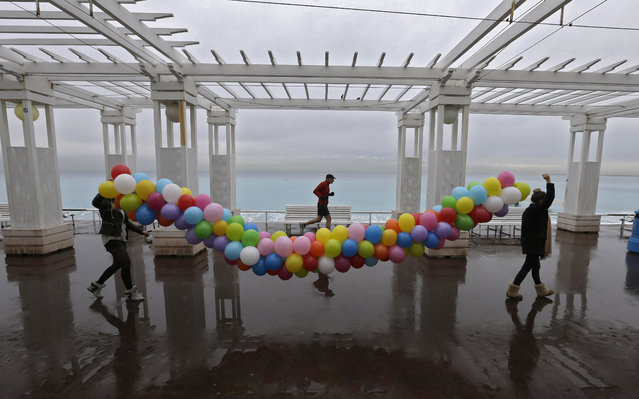 """Two employees of Nice town hall, carry a string of balloons on the Promenade des Anglais, in Nice, southeastern France, Friday, February 6, 2015. Balloons designed for the Foundation """"Hospitals Paris-France"""", chaired by Bernadette Chirac, former France's President Jacques Chirac's wife, organized every year, the """"Yellow coins operation"""" to improve the lives of hospitalized children and adolescents. (Photo by Lionel Cironneau/AP Photo)"""