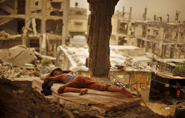 A Palestinian boy sleeps on a mattress inside the remains of his family's house, that witnesses said was destroyed by Israeli shelling during a 50-day war in 2014 summer, during a sandstorm in Gaza September 8, 2015. (Photo by Suhaib Salem/Reuters)