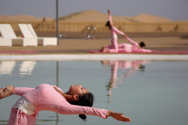 Dancers perform yoga near a swimming pool in Xiangshawan Desert, also called Sounding Sand Desert on July 20, 2013 in Ordos of Inner Mongolia Autonomous Region, China. Xiangshawan is China's famous tourist resort in the desert. It is located along the middle section of Kubuqi Desert on the south tip of Dalate League under Ordos City. Sliding down from the 110-metre-high, 45-degree sand hill, running a course of 200 metres, the sands produce the sound of automobile engines, a natural phenomenon that nobody can explain. (Photo by Feng Li/Getty Images)