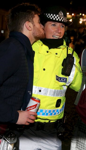 A man kisses a police officer during the Hogmanay celebrations in Edinburgh, Scotland, December 31, 2015. (Photo by Russell Cheyne/Reuters)