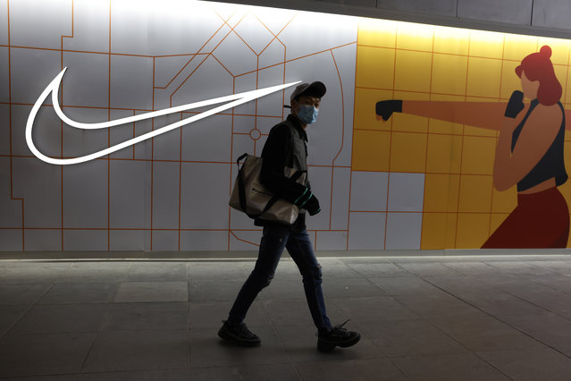 A visitor to a mall wearing a mask past by a Nike store in Beijing on Monday, March 29, 2021. (Photo by Ng Han Guan/AP Photo)