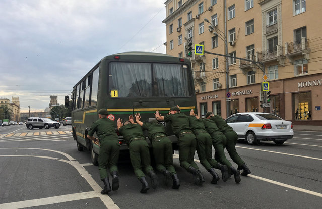 Russian servicemembers push a bus along an avenue in Moscow, Russia on August 20, 2018. (Photo by Maxim Shemetov/Reuters)