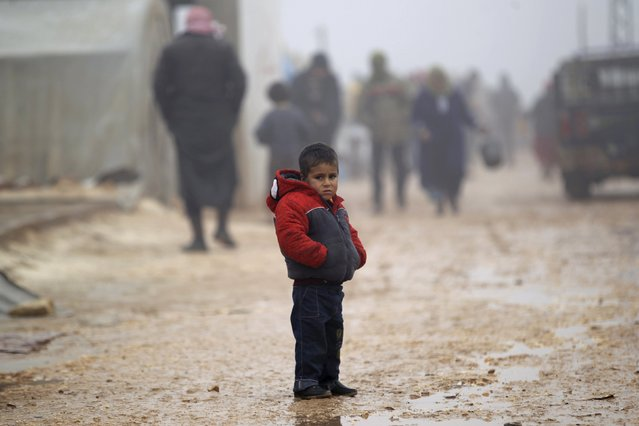 A boy stands outside tents housing internally displaced people, during the cold weather in Jerjnaz camp, in Idlib province, Syria, January 5, 2016. (Photo by Khalil Ashawi/Reuters)