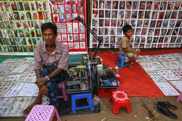 A street tattoo artist and his son wait for customers at the Kyaik-Khauk pagoda festival in the Tanlyin township outside Yangon February 4, 2015. (Photo by Soe Zeya Tun/Reuters)