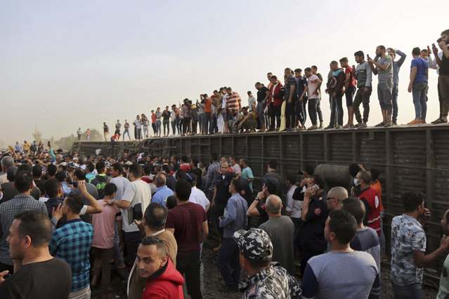 People gather at the site where a passenger train derailed injuring at least 100 people, in Banha, Qalyubia province, Egypt, Sunday, April 18, 2021. (Photo by Fadel Dawood/AP Photo)