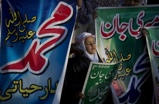 A Pakistani girl stands amid banners that carry the name of the Prophet Muhammad during a rally organized by the religious party Jamaat-e-Islami to condemn the French weekly magazine Charlie Hebdo for publication of caricatures of Muhammad, in Islamabad, Pakistan, Friday, January 30, 2015. (Photo by B. K. Bangash/AP Photo)
