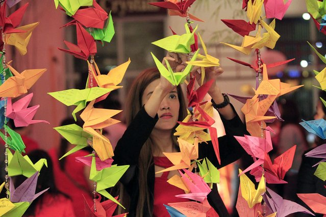 A woman hangs a paper crane with her wish written on it during Chinese New Year eve celebrations at Chinatown in Manila February 18, 2015. (Photo by Romeo Ranoco/Reuters)