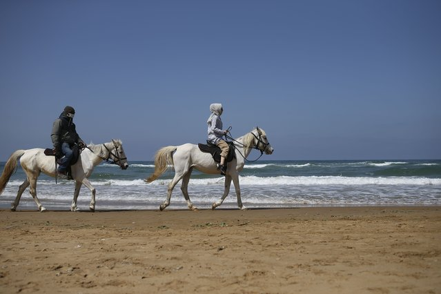 """People ride horses on the beach in Kilyos, northern Istanbul, Thursday, April 29, 2021, a few hours before the start of the latest lockdown to help protect from the spread of the coronavirus. People stocked up on groceries, shoppers filled markets and many left cities for their hometowns or the southern coast as Turkey's strictest COVID-19 lockdown yet came into effect late Thursday. President Recep Tayyip Erdogan imposed a """"full lockdown"""" until May 17 amid soaring COVID-19 infections and deaths. Turkey now ranks among the world's worst-hit countries and it's the first time that it is imposing a nearly three-week lockdown for the whole of the country. (Photo by Emrah Gurel/AP Photo)"""
