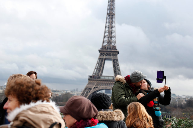 A couple kiss in front of the Eiffel Tower, during Valentine's day in Paris, Saturday, February 14, 2015. Valentine's Day is observed on February 14 each year as a special day to celebrate love and romance. (Photo by Thibault Camus/AP Photo)