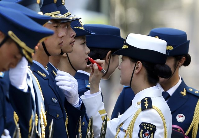 A female honour guard has lipstick applied during preparations for an official welcoming ceremony for Italy's Prime Minister Matteo Renzi outside the Great Hall of the People in Beijing in this June 11, 2014 file photo. (Photo by Jason Lee/Reuters)