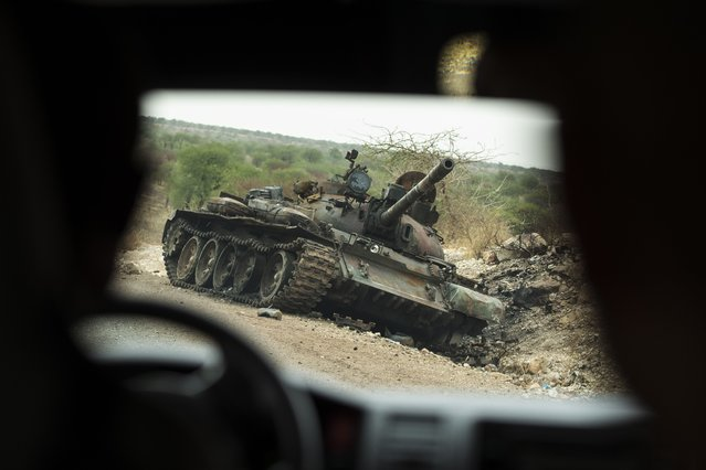 A destroyed tank is seen by the side of the road south of Humera, in an area of western Tigray annexed by the Amhara region during the ongoing conflict, in Ethiopia, Saturday, May 1, 2021. Ethiopia faces a growing crisis of ethnic nationalism that some fear could tear Africa's second most populous country apart, six months after the government launched a military operation in the Tigray region to capture its fugitive leaders. (Photo by Ben Curtis/AP Photo)
