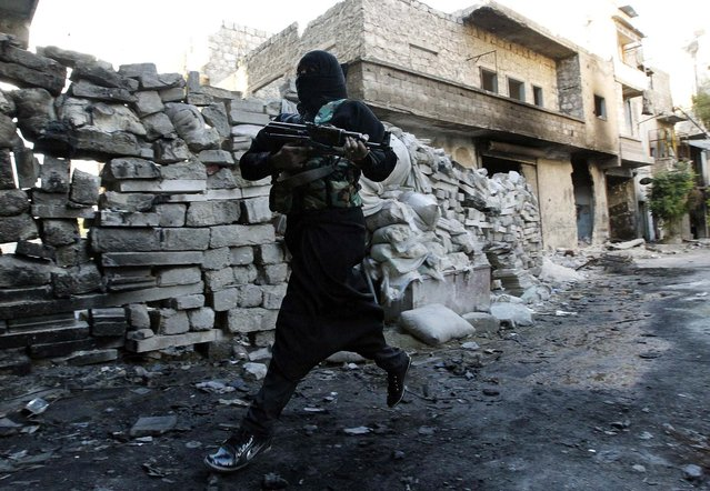 """Um Radwan, a female fighter in the """"Free Syrian Army"""", runs for cover from snipers loyal to the Syrian regime in Aleppo's Bustan al-Basha district, on October 3, 2013. Um Radwan joined the Free Syrian Army after the death of her husband, who was also a Free Syrian Army fighter, according to activists. (Photo by Muzaffar Salman/Reuters)"""