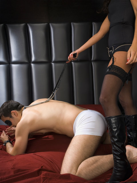 Dominatrix holding leash around man's neck. (Photo by Getty Images)