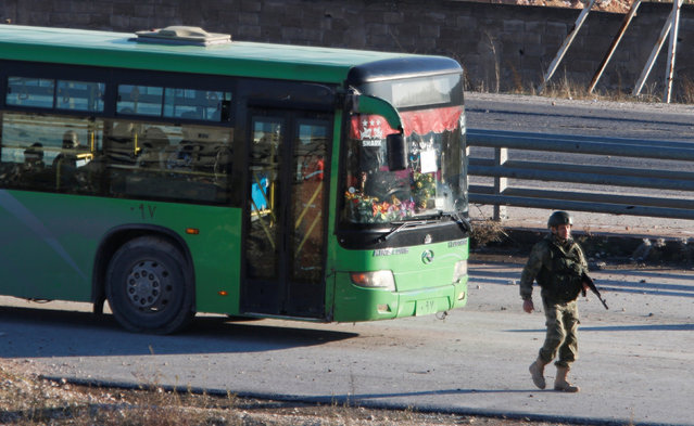 A bus evacuating people from a rebel-held part of eastern Aleppo, is seen driving past a member of forces loyal to Syria's President Bashar al-Assad, Syria December 15, 2016. (Photo by Omar Sanadiki/Reuters)