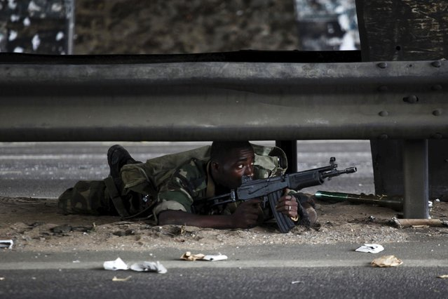 A soldier loyal to Ivory Coast presidential claimant Alassane Ouattara lies on a road as fighting flares across the country's main city Abidjan April 4, 2011. (Photo by Emmanuel Braun/Reuters)