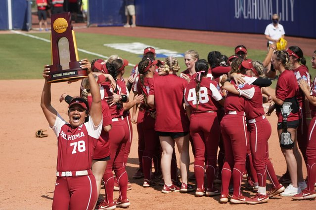 Oklahoma's Jocelyn Alo (78) carries the championship trophy toward the Oklahoma fans as the team celebrates after defeating Florida State in the final game of the NCAA Women's College World Series softball championship series Thursday, June 10, 2021, in Oklahoma City. (Photo by Sue Ogrocki/AP Photo)