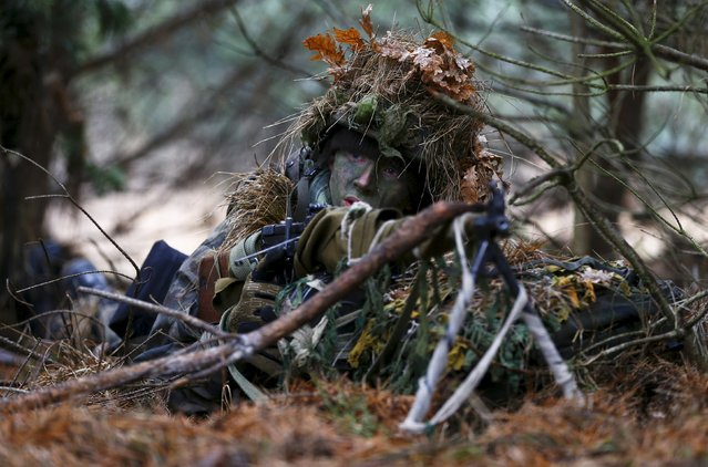 Damian Trynkiewicz prepares his weapon during territorial defence training organised by SJS Strzelec (Shooters Association), paramilitary group in the forest near Minsk Mazowiecki, eastern Poland March 14, 2014. (Photo by Kacper Pempel/Reuters)