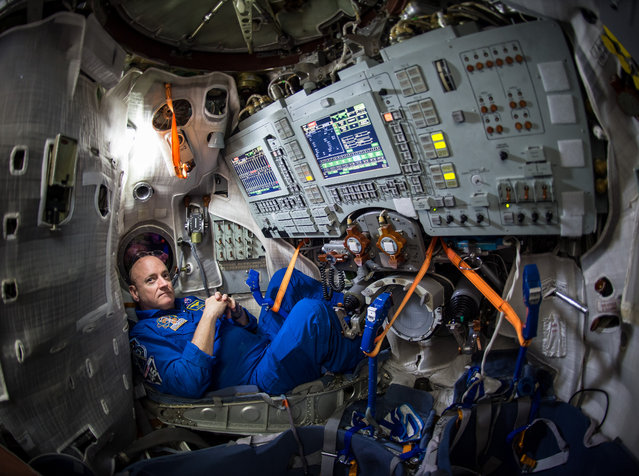 In this photo provided by NASA, astronaut Scott Kelly sits inside a Soyuz simulator at the Gagarin Cosmonaut Training Center (GCTC), Wednesday, March 4, 2015 in Star City, Russia. On Friday, March 28, 2015, Kelly and cosmonaut Mikhail Kornienko will travel to the International Space Station to begin a year-long mission living in orbit. (Photo by Bill Ingalls/AP Photo/NASA)