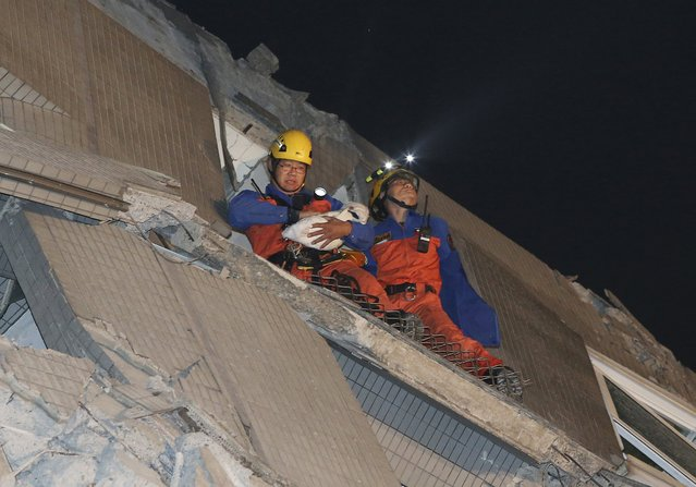 Rescue workers carry a baby swaddled in a cloth from the rubble of a toppled building after an earthquake in Tainan, Taiwan, Saturday, February 6, 2016. (Photo by AP Photo)