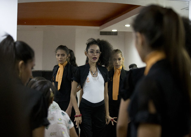In this June 20, 2018 photo, a teacher explains to her students how to walk on a catwalk during a class at Belankazar Modeling Academy, in Caracas, Venezuela. As the nation plummets into economic ruin, even more young women are holding fast to dreams of becoming beauty queens. (Photo by Fernando Llano/AP Photo)