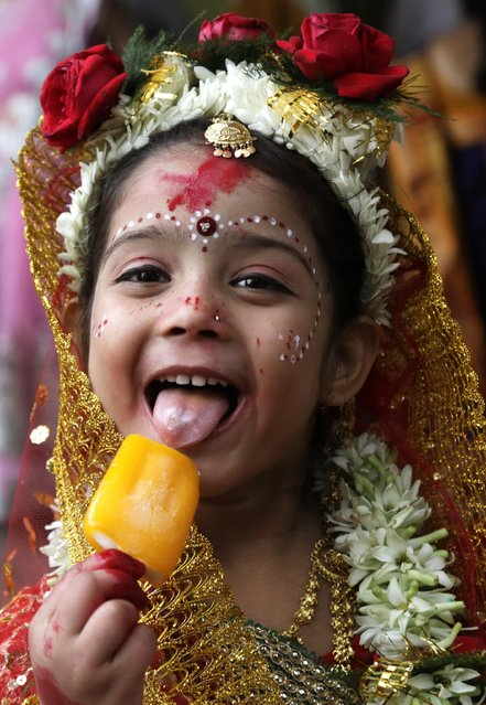 """A young Hindu girl eats an ice-cream before participating in a ceremony where she and other girls  will be worshipped as """"Kumari"""", or living goddess, during Ram Navami festival, at a temple in Kolkata, India, Saturday, March 28, 2015. (Photo by Bikas Das/AP Photo)"""