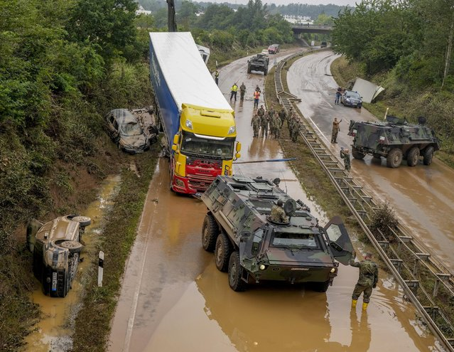 German army soldiers work on flooded cars and a truck on a road in Erftstadt, Germany, Saturday, July 17, 2021. (Photo by Michael Probst/AP Photo)
