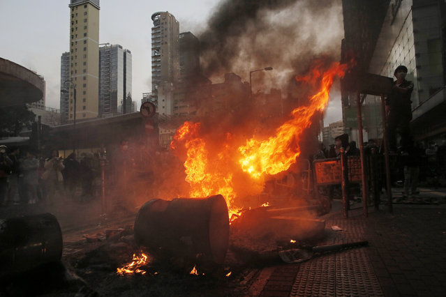 Smoke rises as rioters set fires on a street in Mongkok district of Hong Kong, Tuesday, February 9, 2016. (Photo by Vincent Yu/AP Photo)