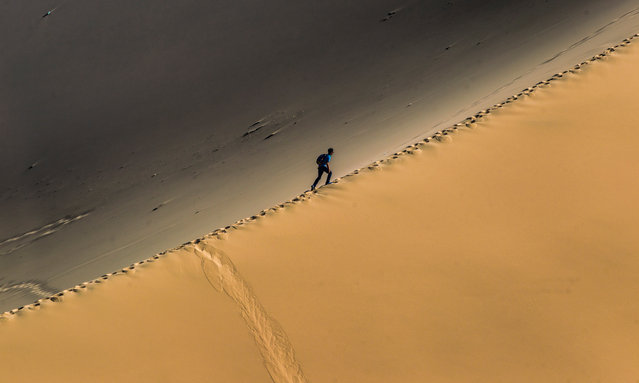 A man climbs dunes near Crescent Lake in Dunhuang, Gansu Province, China, 27 September 2018. Dunhuang is a city in northwestern Gansu Province, Western China. City was major stop on the ancient Silk Road, established in an oasis which contains Crescent Lake and had strategic position on a crossroads of the Southern Route of Silk Road and main road from India trough Tibet and Mongolia to Southern Siberia. (Photo by Aleksander Plavevski/EPA/EFE)