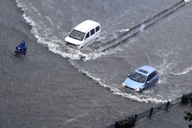 In this photo released by Xinhua News Agency, vehicles pass through floodwaters in Zhengzhou in central China's Henan Province on Tuesday, July 20, 2021. At least a dozen people died in severe flooding Tuesday in a Chinese provincial capital that trapped people in subways and schools, washed away vehicles and stranded people in their workplaces overnight. (Photo by Zhu Xiang/Xinhua via AP Photo)