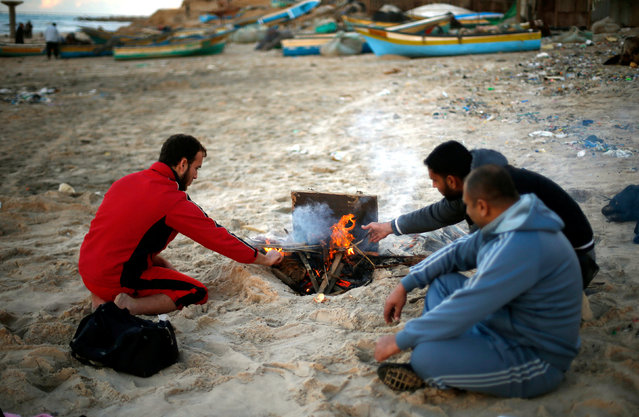 Palestinian warm themselves at the beach of northern Gaza Strip December 17, 2016. (Photo by Suhaib Salem/Reuters)