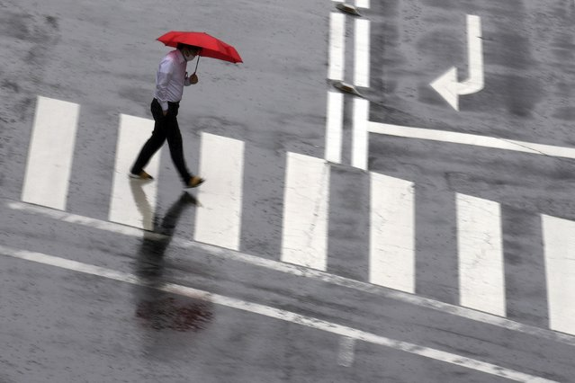 A man wearing a protective mask to help curb the spread of the coronavirus walks along a pedestrian crossing in a sudden rain Thursday, June 17, 2021, in Tokyo. (Photo by Eugene Hoshiko/AP Photo)