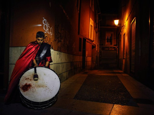 """A young penitent plays his drum as he rests on a corner of one old street in the procession of the """"Santa Veracruz"""" brotherhood, during Holy Week in Calahorra, northern Spain, Tursday, April 2, 2015. (Photo by Alvaro Barrientos/AP Photo)"""