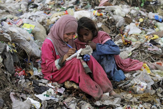 A Pakistani scavenger girl writes on a notebook she collected from a garbage, while another girl sits next to her in Lahore, Pakistan, Wednesday, April 1, 2015. Thousands of children pick recyclable items from waste dumping points to earn living for their poor families. (Photo by K. M. Chaudary/AP Photo)