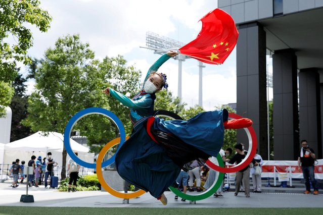 Mongolian Chinese performs a traditional Chinese dance in front of the Olympic Rings located near the National Stadium, the main stadium for the 2020 Tokyo Olympic Games in Tokyo, Japan July 29 2021. (Photo by Androniki Christodoulou/Reuters)