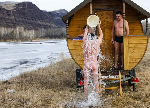 A friend of local resident Valentin Krasin cools off with cold water after a steam bath in his mobile bathing station on the banks of the Tuba river in Siberia, on December 1, 2013. Krasin designed and constructed the mobile bathing station based on a traditional Russian steam bath, intending it for trips with friends and possibly as a small commercial venture. (Photo by Ilya Naymushin/Reuters)