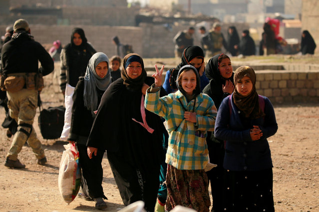 Displaced Iraqi civilians, who fled the Islamic State stronghold of Mosul, walk in the Mithaq district of eastern Mosul, Iraq, January 3, 2017. (Photo by Thaier Al-Sudani/Reuters)