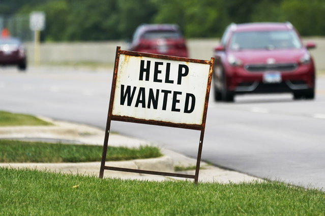 A help wanted sign is displayed at a gas station in Mount Prospect, Ill., Tuesday, July 27, 2021.  The number of Americans applying for unemployment benefits fell last week by 14,000 to 385,000, Thursday, Aug. 5,  more evidence that the economy and the job market are rebounding briskly from the coronavirus recession. (Photo by Nam Y. Huh/AP Photo)