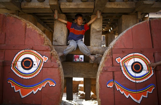 A boy plays on the chariot of God Bhairab before pulling the chariot during the Bisket festival at Bhaktapur April 10, 2015. (Photo by Navesh Chitrakar/Reuters)