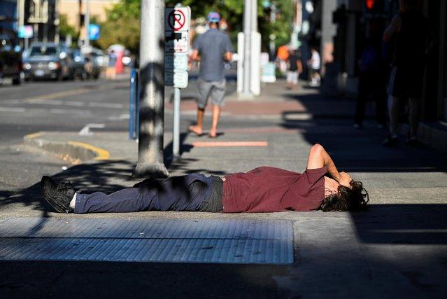 A man lies on a sidewalk during a heatwave in Portland, Oregon, U.S., August 11, 2021. (Photo by Mathieu Lewis-Rolland/Reuters)